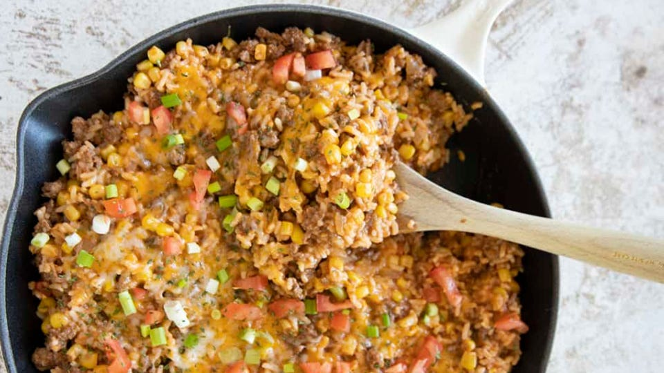 A cast-iron skillet full of Mexican rice casserole.