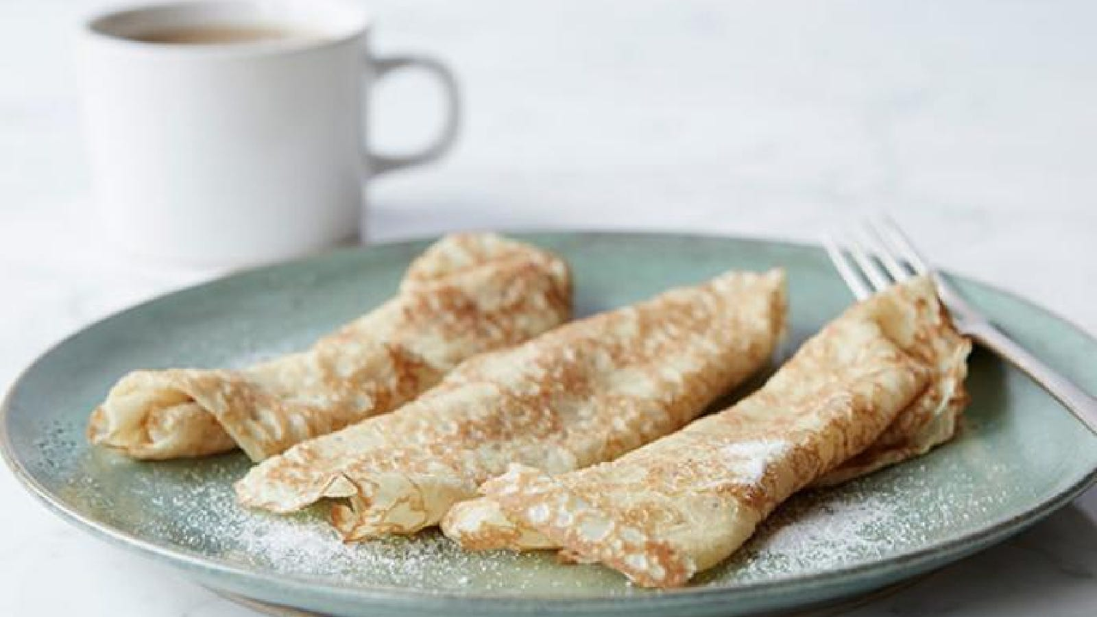 Three crêpes topped with sugar on a plate next to a coffee mug.