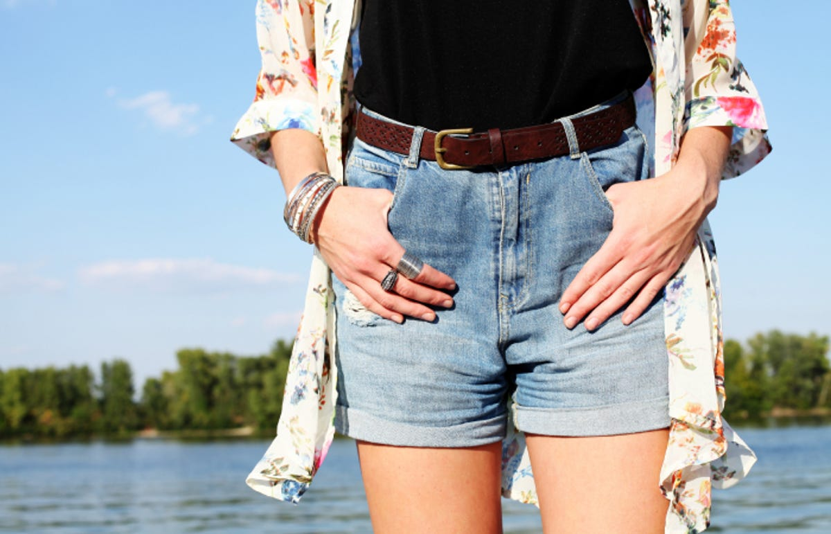 girl in denim shorts with a high waist; river or lake in background