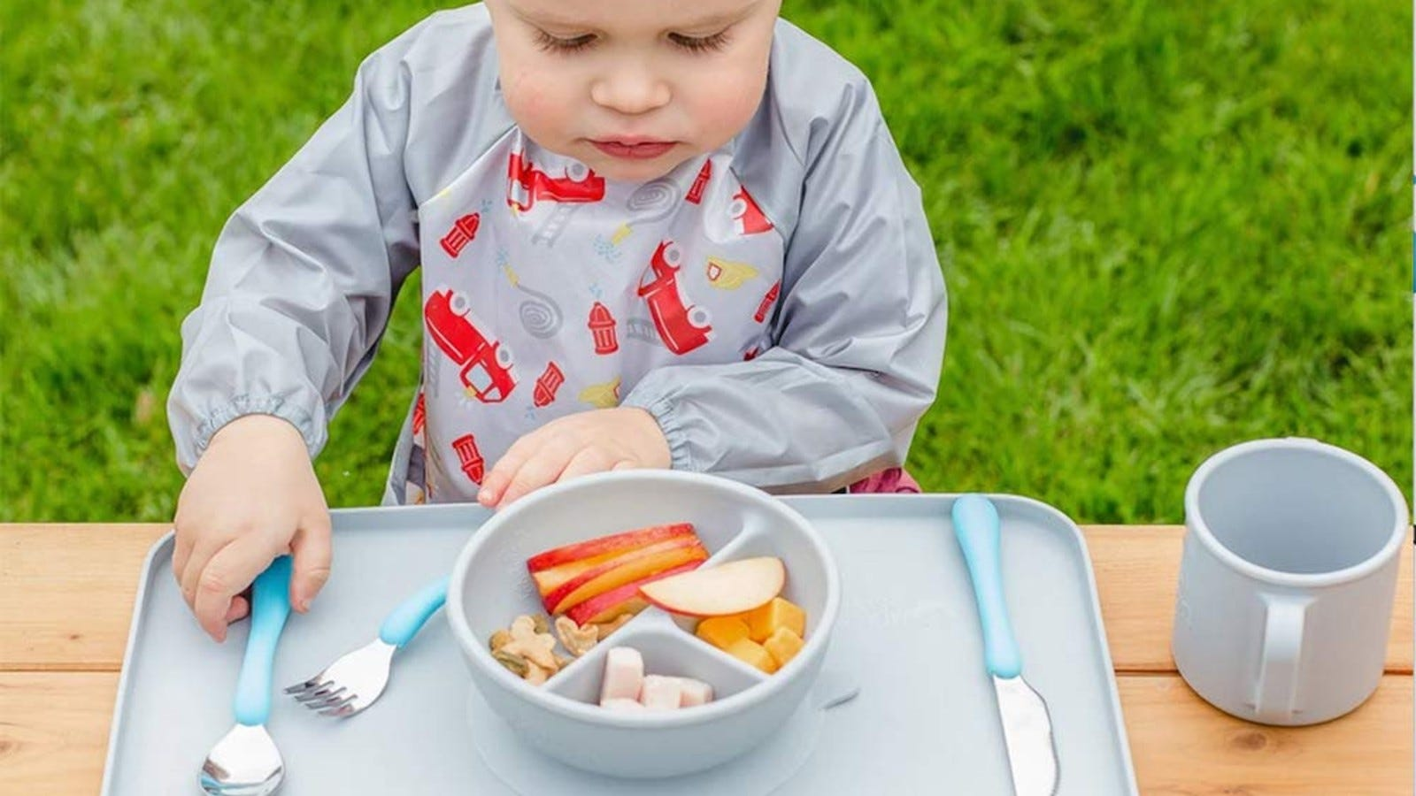 A toddler looking down at the fruits and cheeses in the different sections of the green sprouts Learning Bowl.