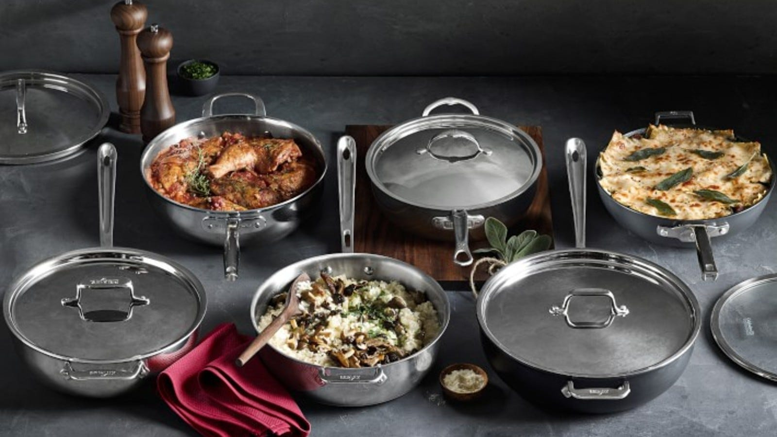 A set of stainless steel pans with freshly cooked food inside.