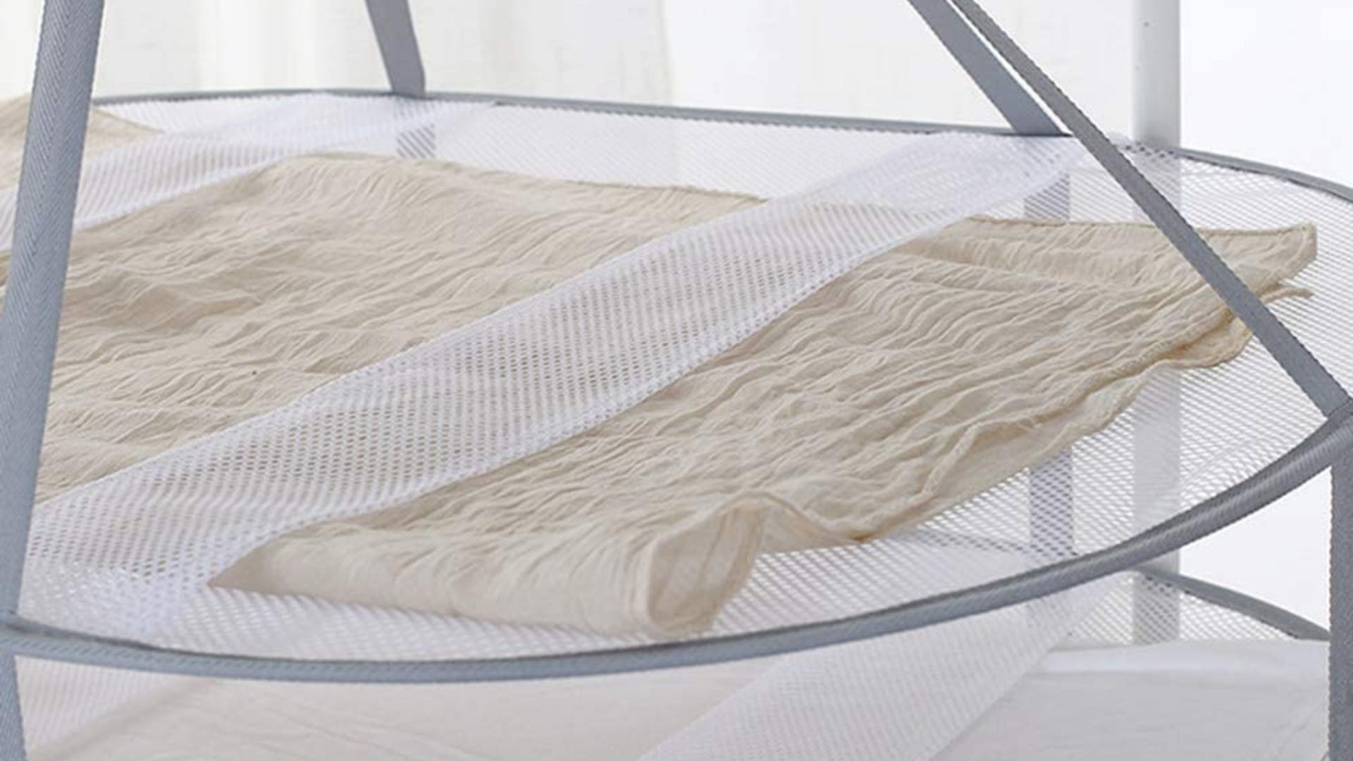 A delicate piece of material lying on a sweater hanging dryer.