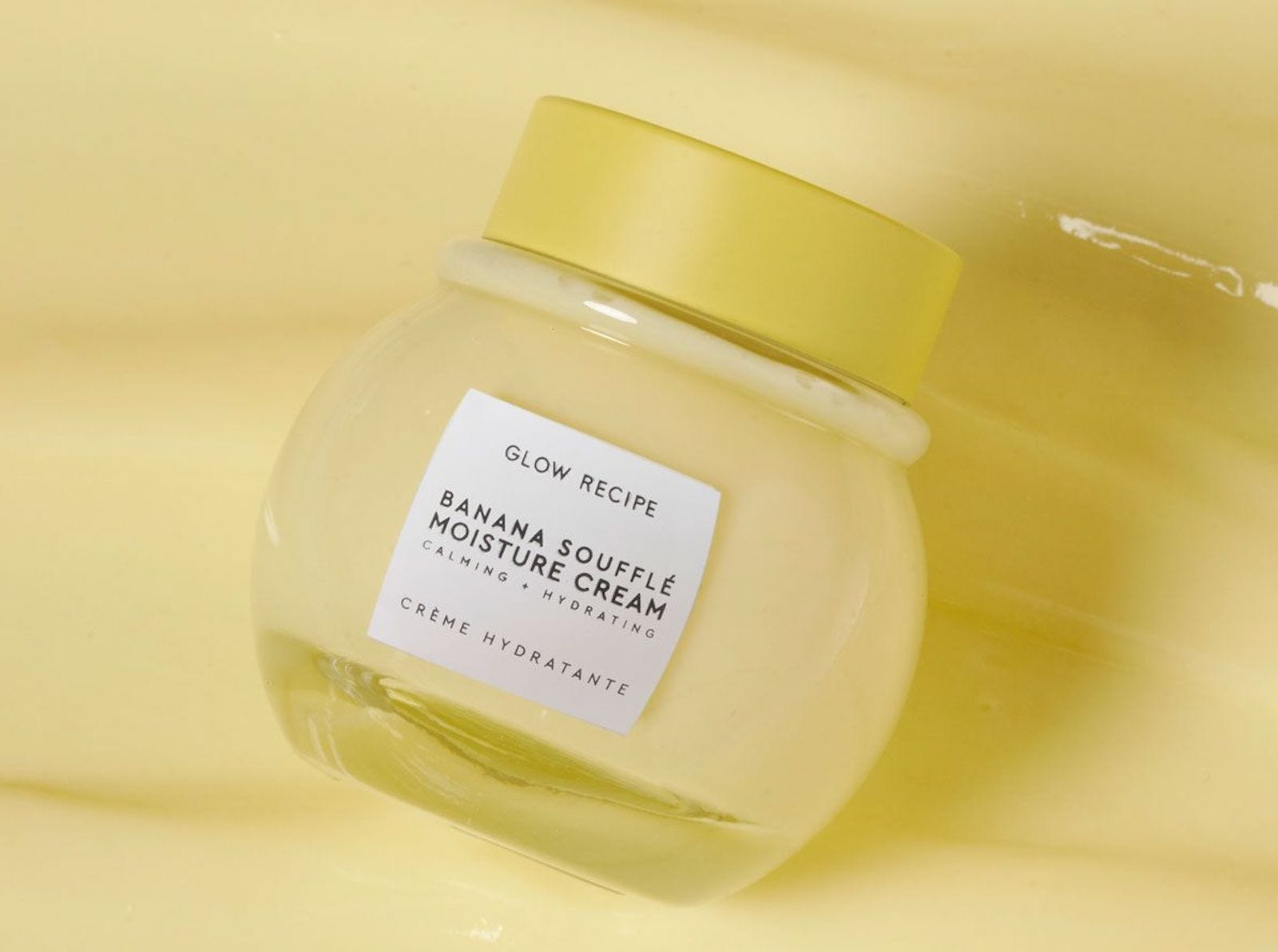 A jar of pale yellow cream, set against a pale yellow background