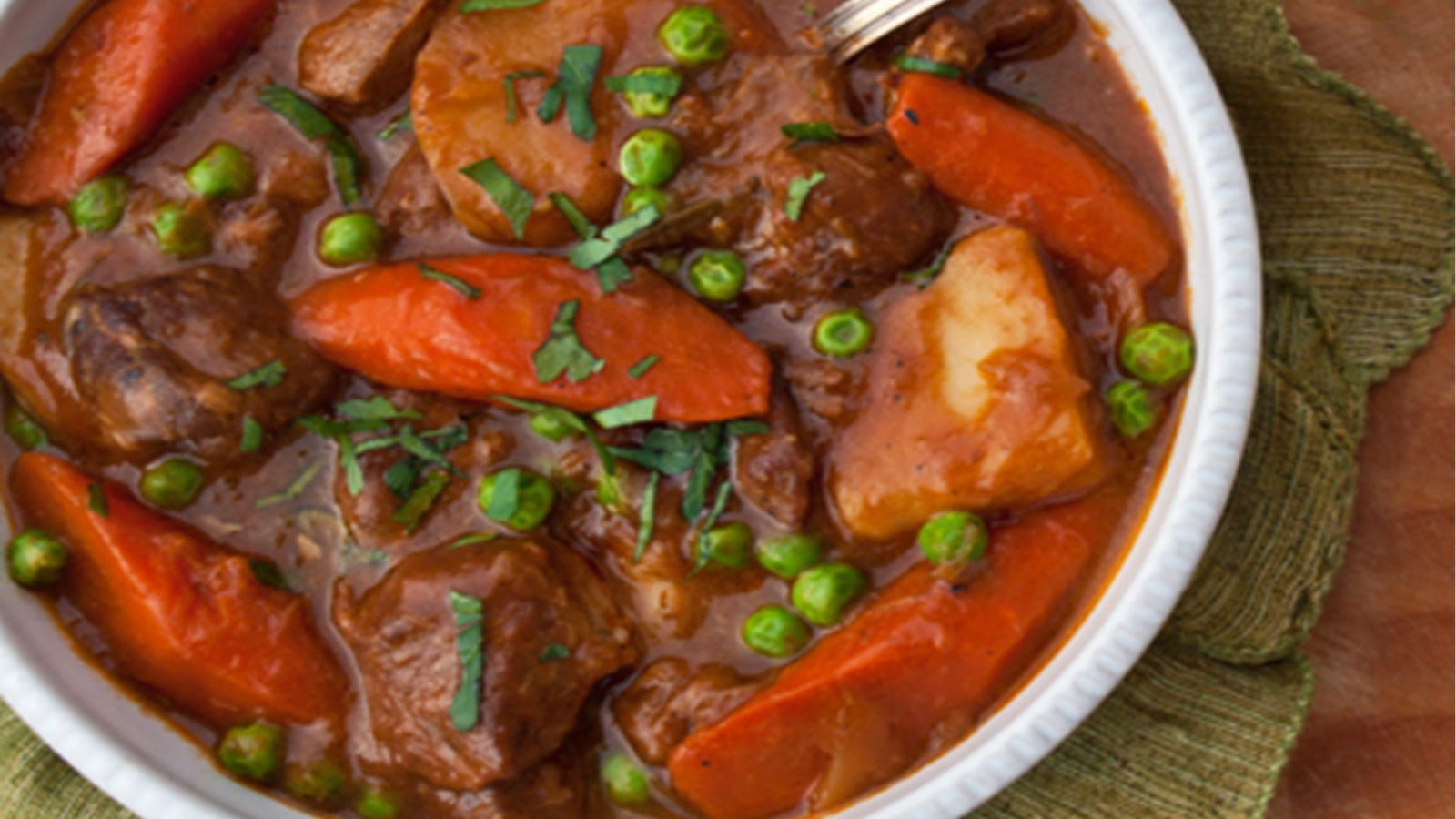 A bowl of Lamb and Guinness stew, filled with carrots, potatoes, and hearty chunks of lamb.
