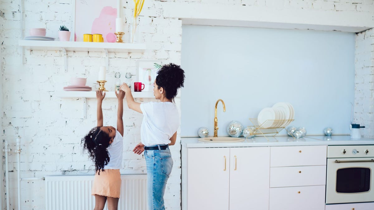 A mother and daughter getting dishes off of an open shelf in the kitchen.