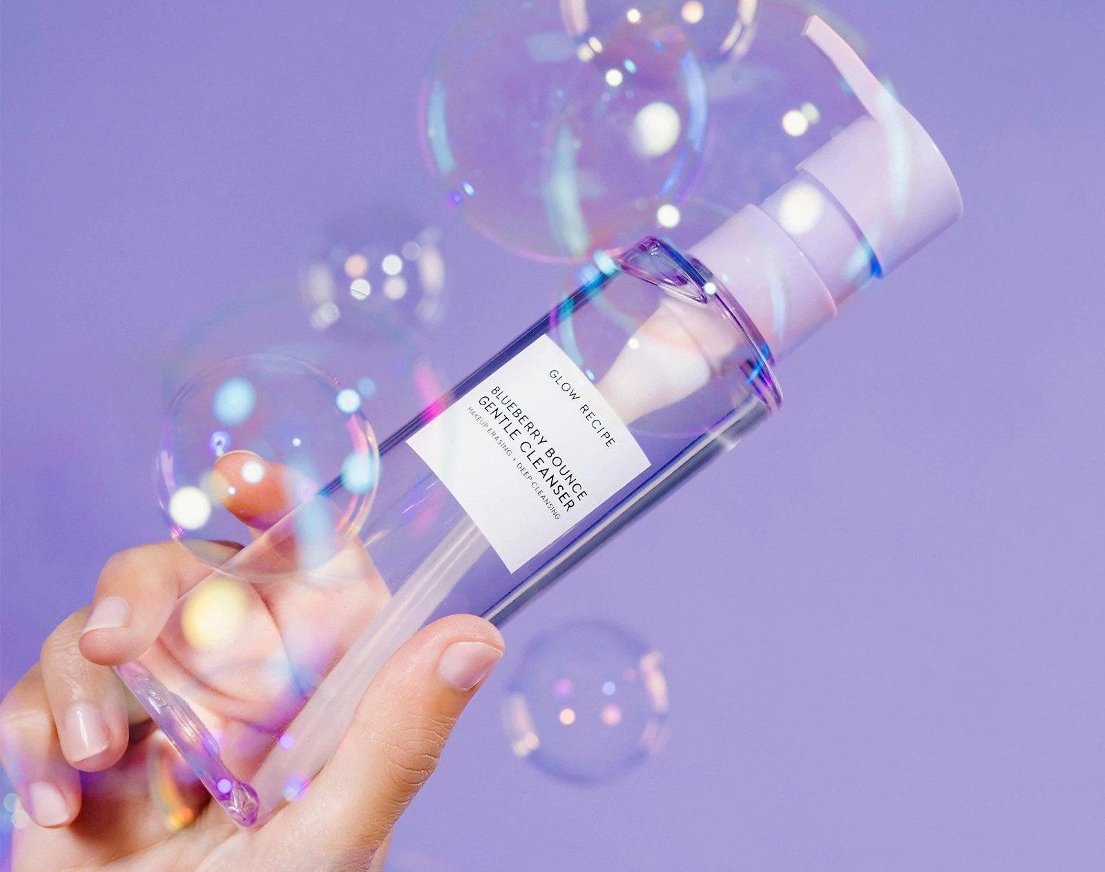 A hand holding up bottle of pale purple liquid cleanser, against a purple background with bubbles