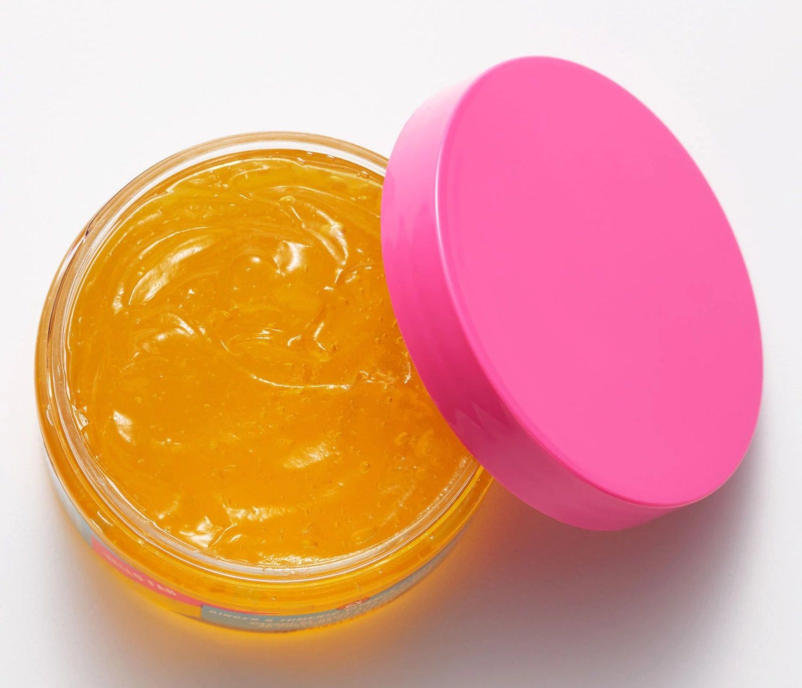 A round vial of an orange jelly substance, with a pink lid tilted half-off