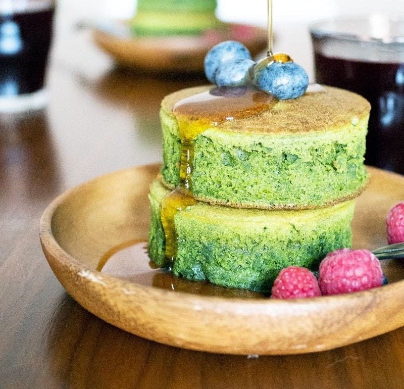 Green-hued, fluffy pancakes sit on a plate with raspberry and blueberry toppings.