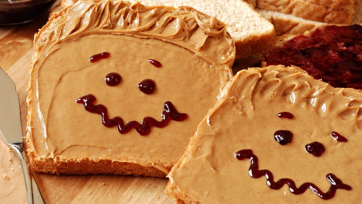 Smiley faces made out of jam on two slices of bread with peanut butter.