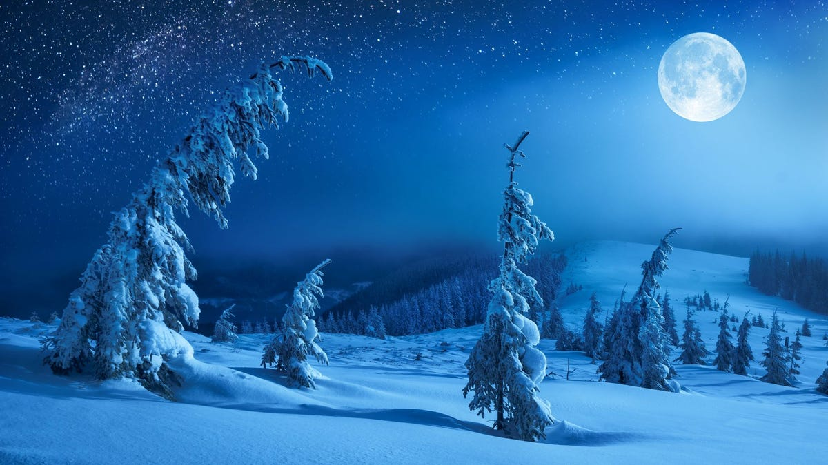 A full moon over a snowy landscape with hills and trees.