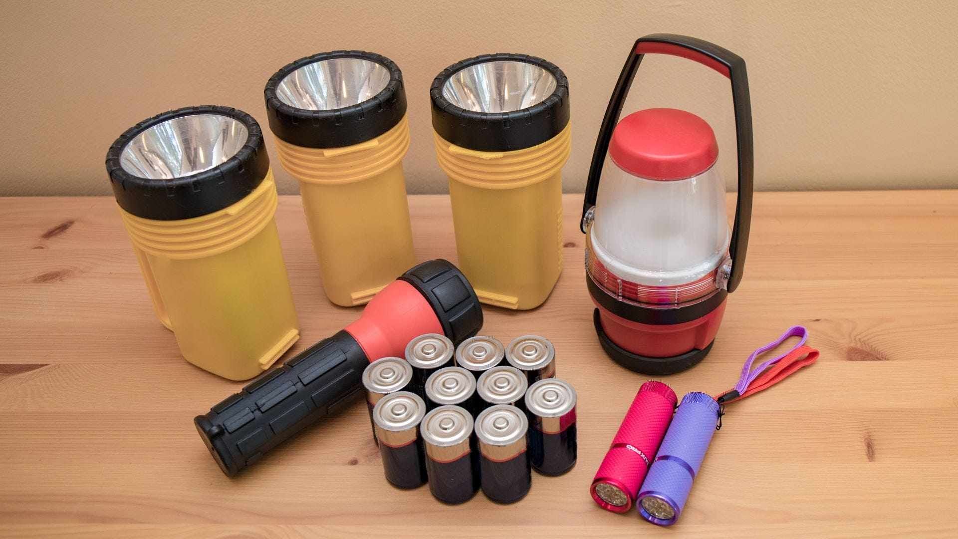 Six flashlights of different sizes, a lantern, and a bunch of batteries on a table.