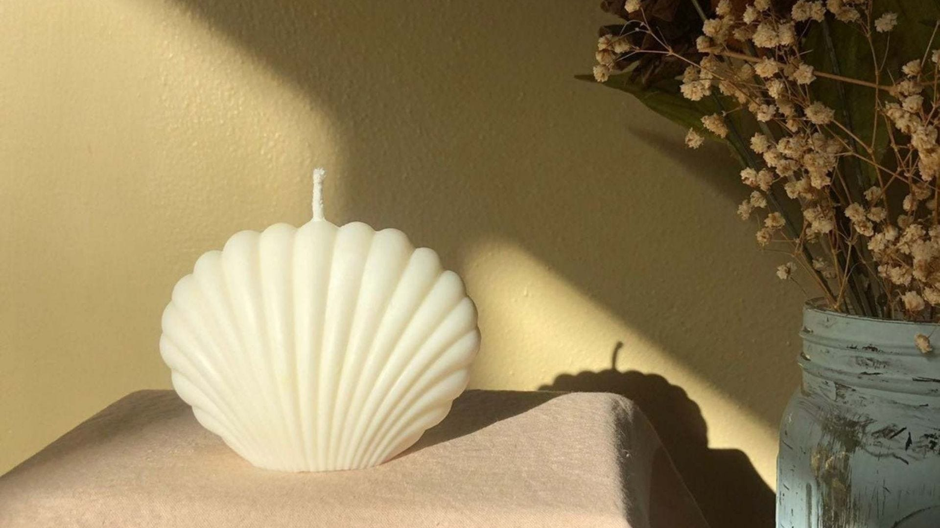 A white seashell candle on a table next to a vase of dried plants.