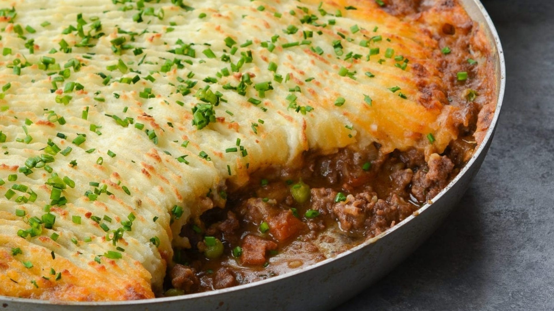 A pan of shepherd's pie with a serving removed, revealing the delicious meaty inside.