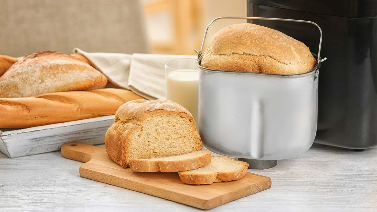 Sliced bread on a cutting board and a loaf in a bread machine.