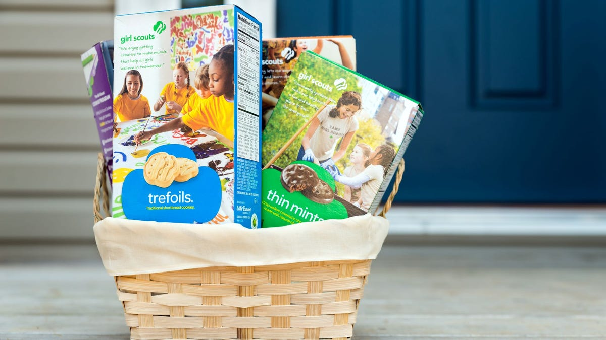A basket full of boxes Girl Scout Cookies sitting on a porch.