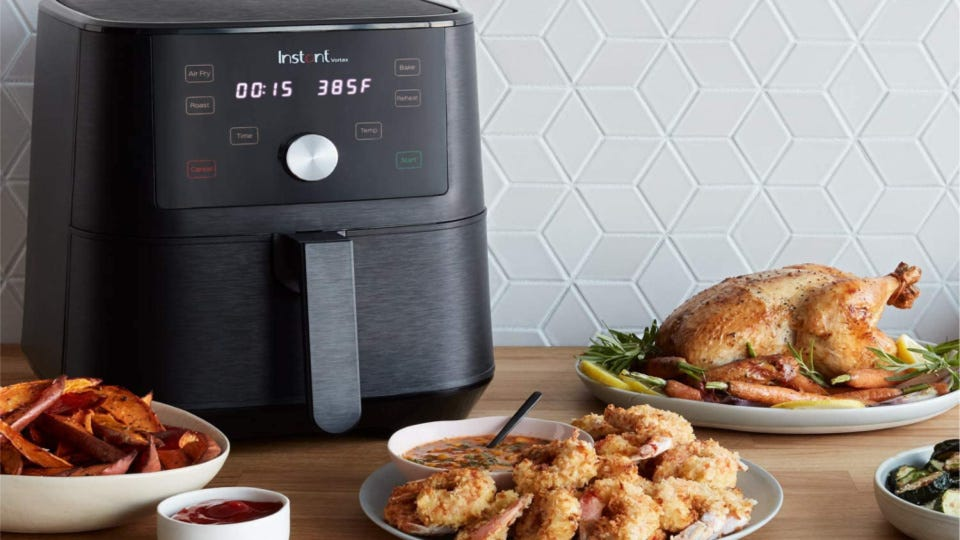 An Instant Vortex, placed on a kitchen counter with recently air-fried foods like fried shrimp, roast chicken and sweet potato wedges.