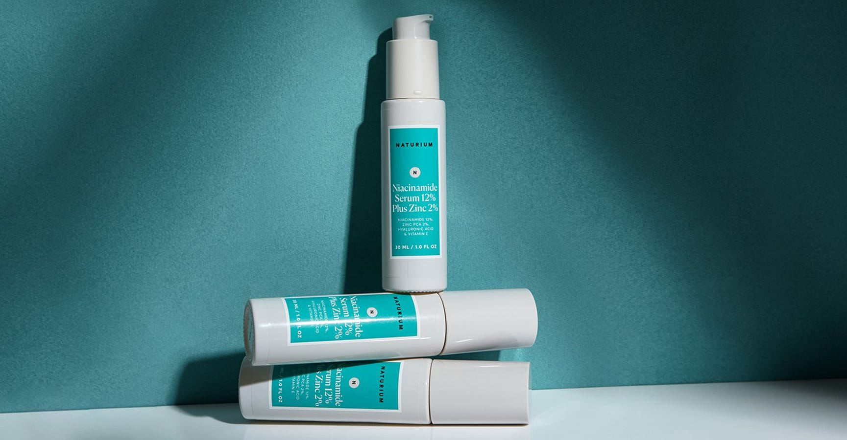 Product shot of a bottle of niacinamide by Naturium standing over two horizontally stacked bottles of the same product in front of a blue background, under the spotlight