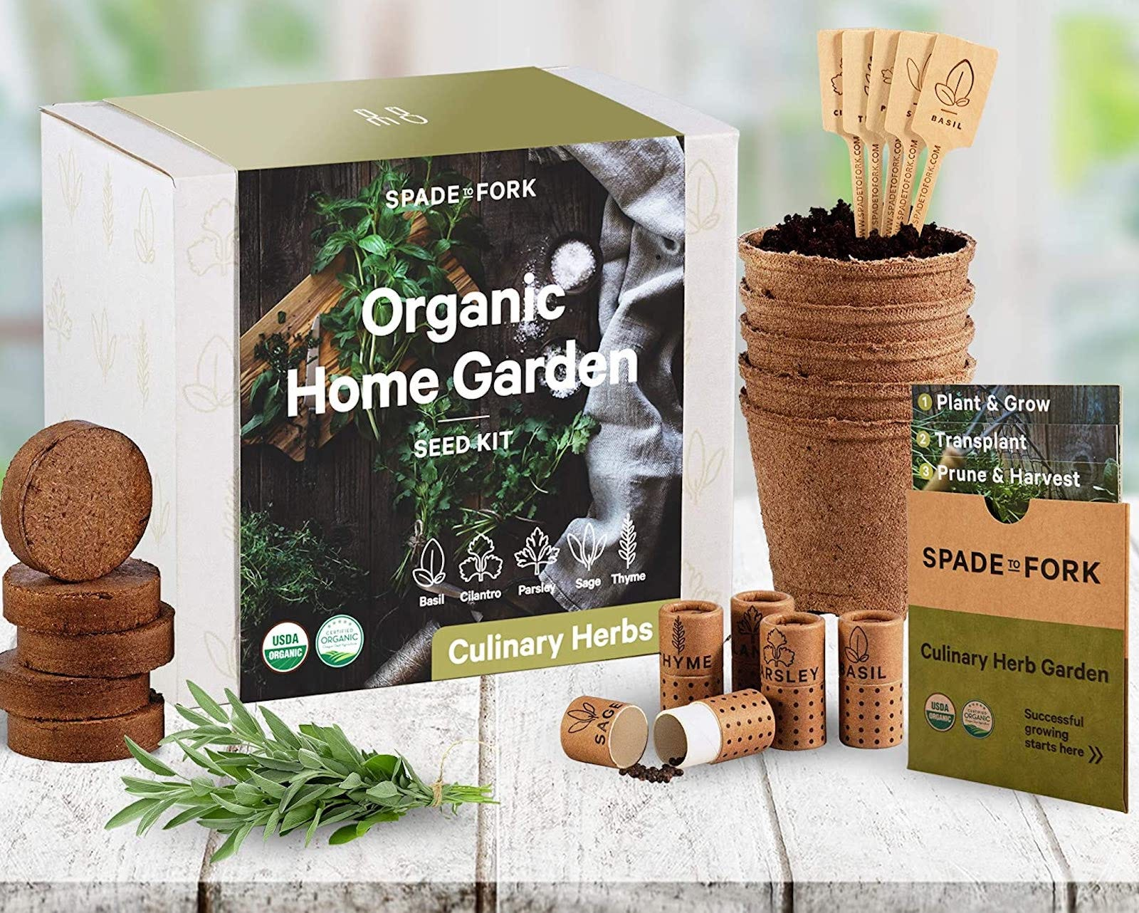 """A box reading """"Organic Home Garden Seed Kit"""" next to soil disks, peat pots, and herb tubes, on a white wood surface"""