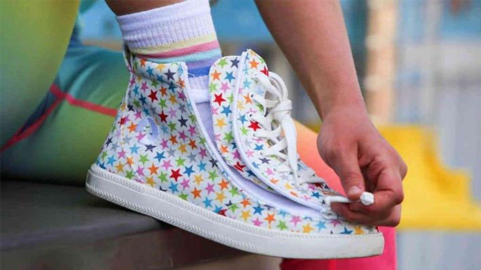 A child zipping a Billy Footwear sneaker.