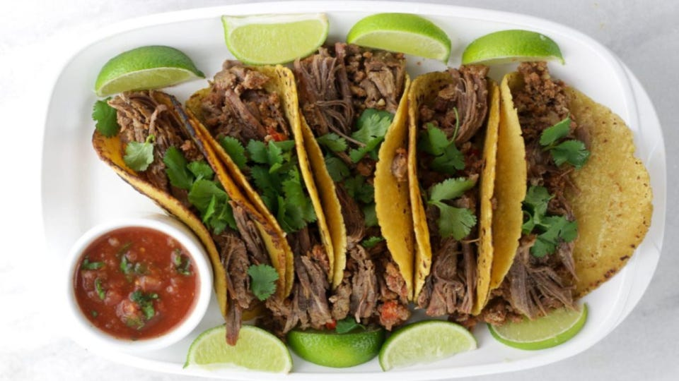 Five shredded beef fajitas, topped with cilantro and lined with lime wedges and a side of salsa.