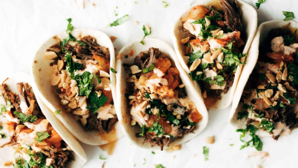Five delicious Korean beef tacos dressed with siracha mayo, peanuts and kimchi, topped with fresh herbs.
