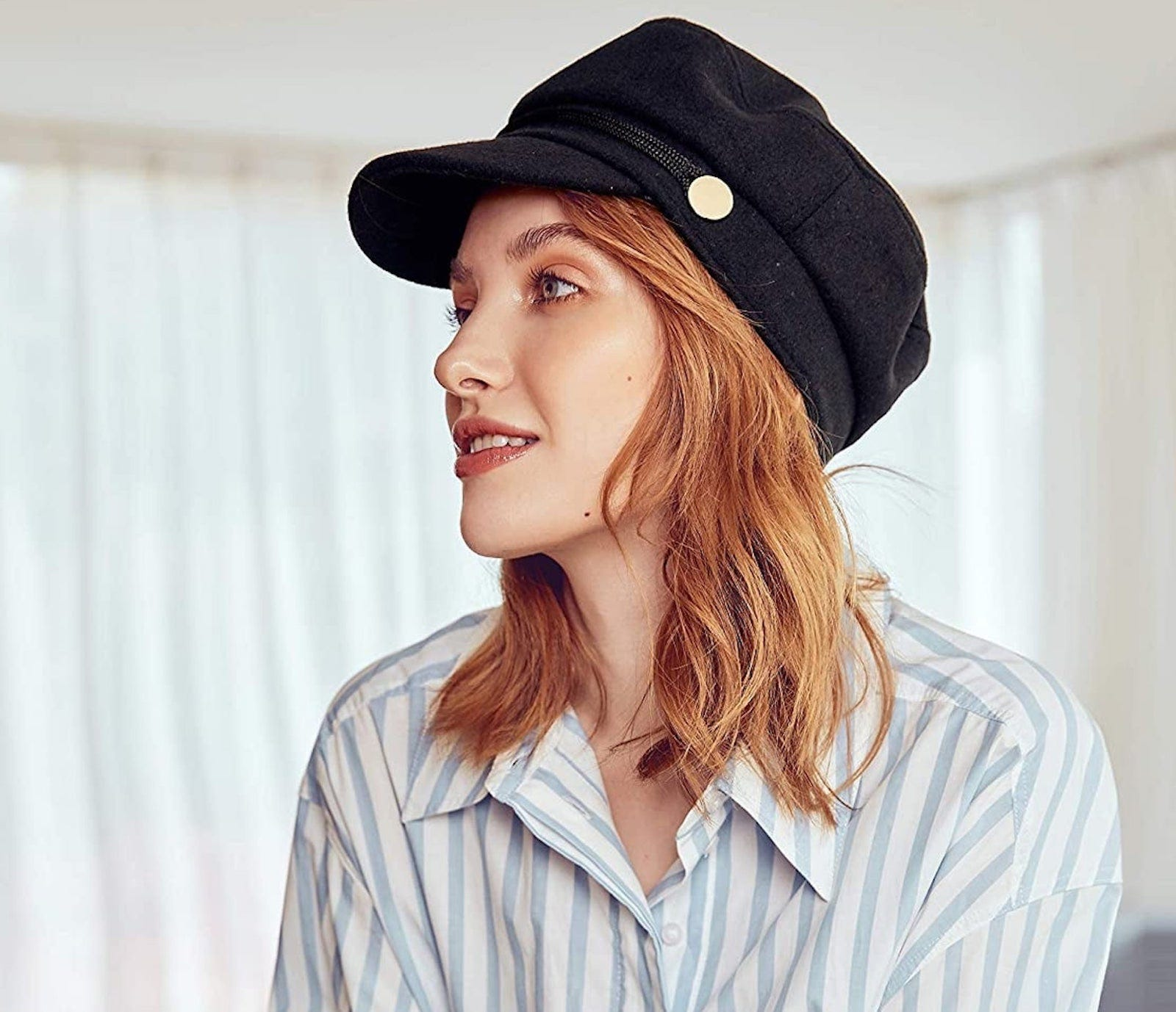 A redhaired white woman is shown in profile, wearing a blue striped shirt and a black newsboy cap