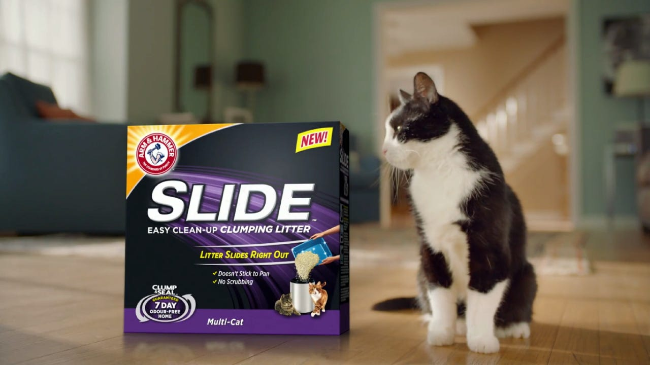 A black and white cat looking at box of Arm & Hammer Slide Litter.