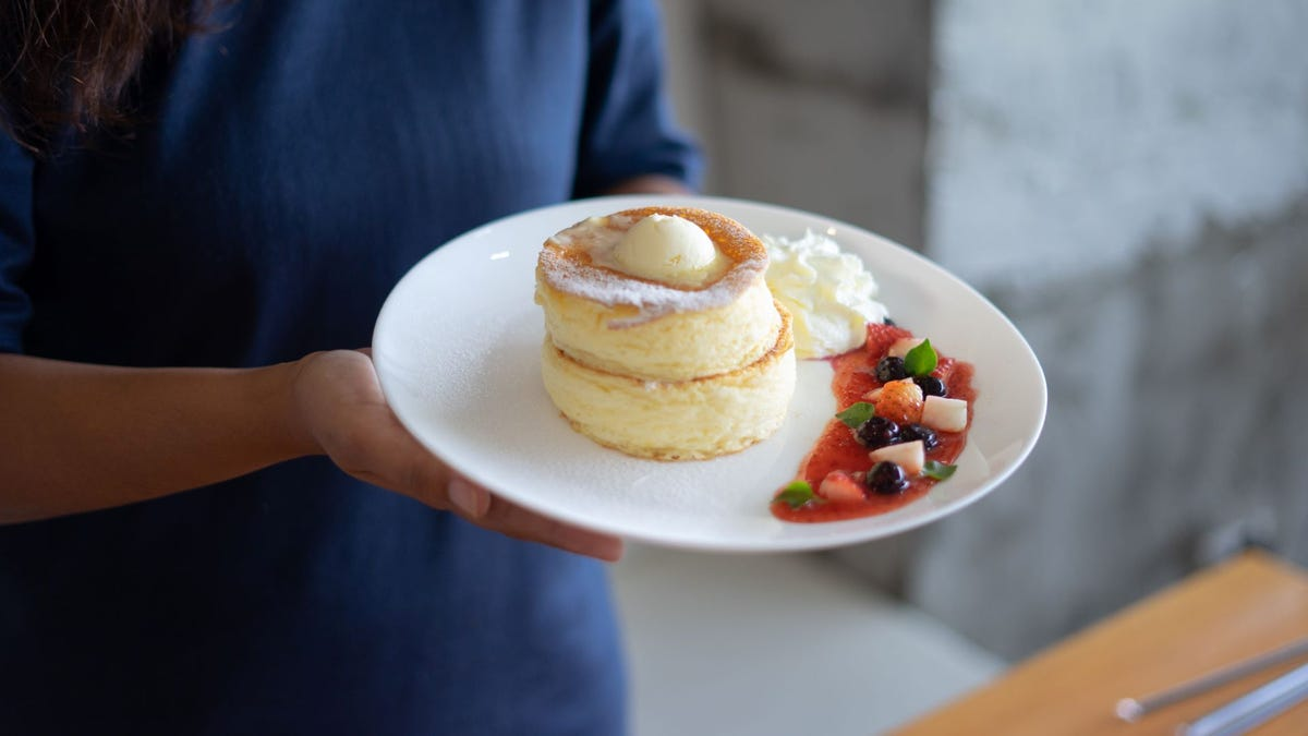 A woman holding a plate of two Japanese pancakes.