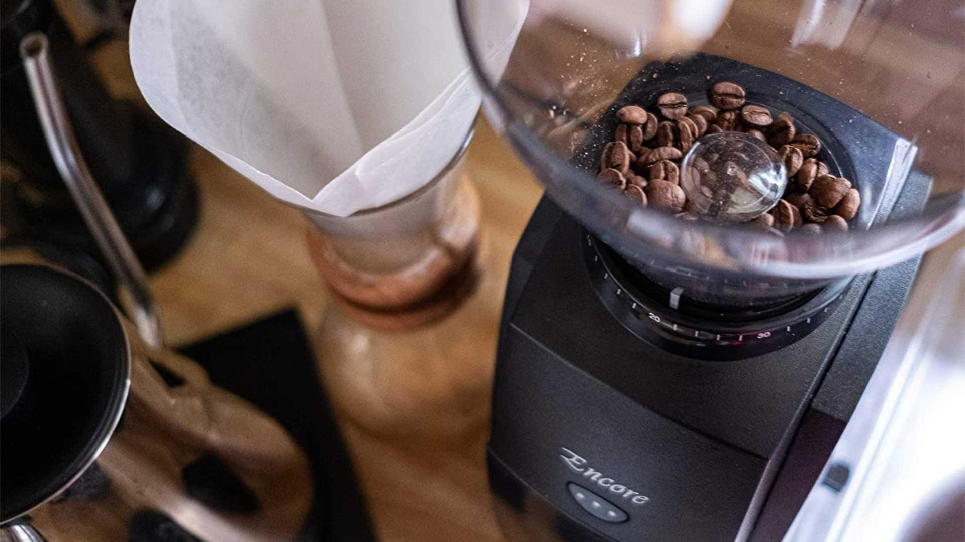 A coffee grinder with beans in the hopper, next to a pour-over coffee maker.
