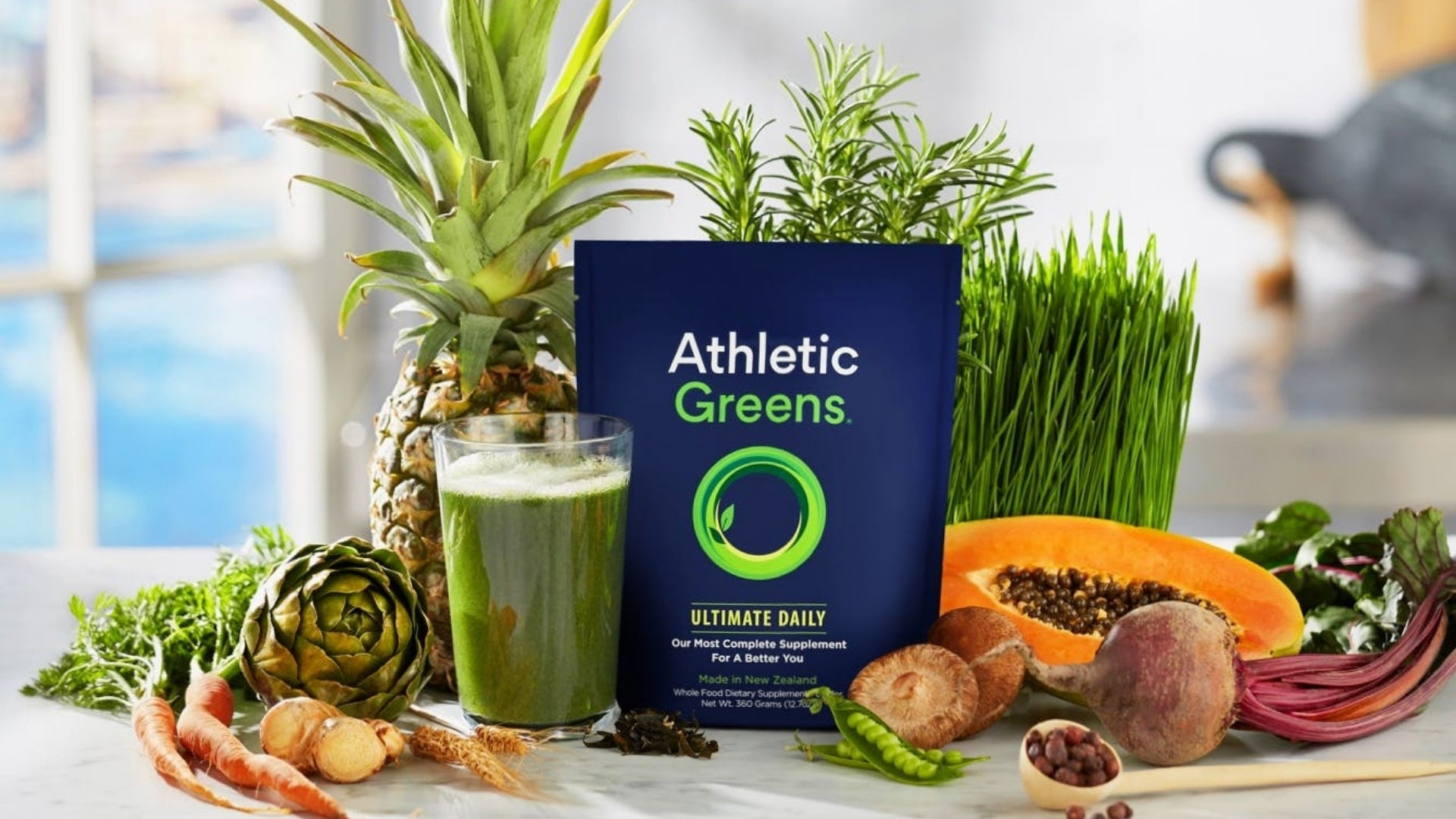 A bag of Athletic Greens Ultimate Daily surrounded by fruits and vegetables.