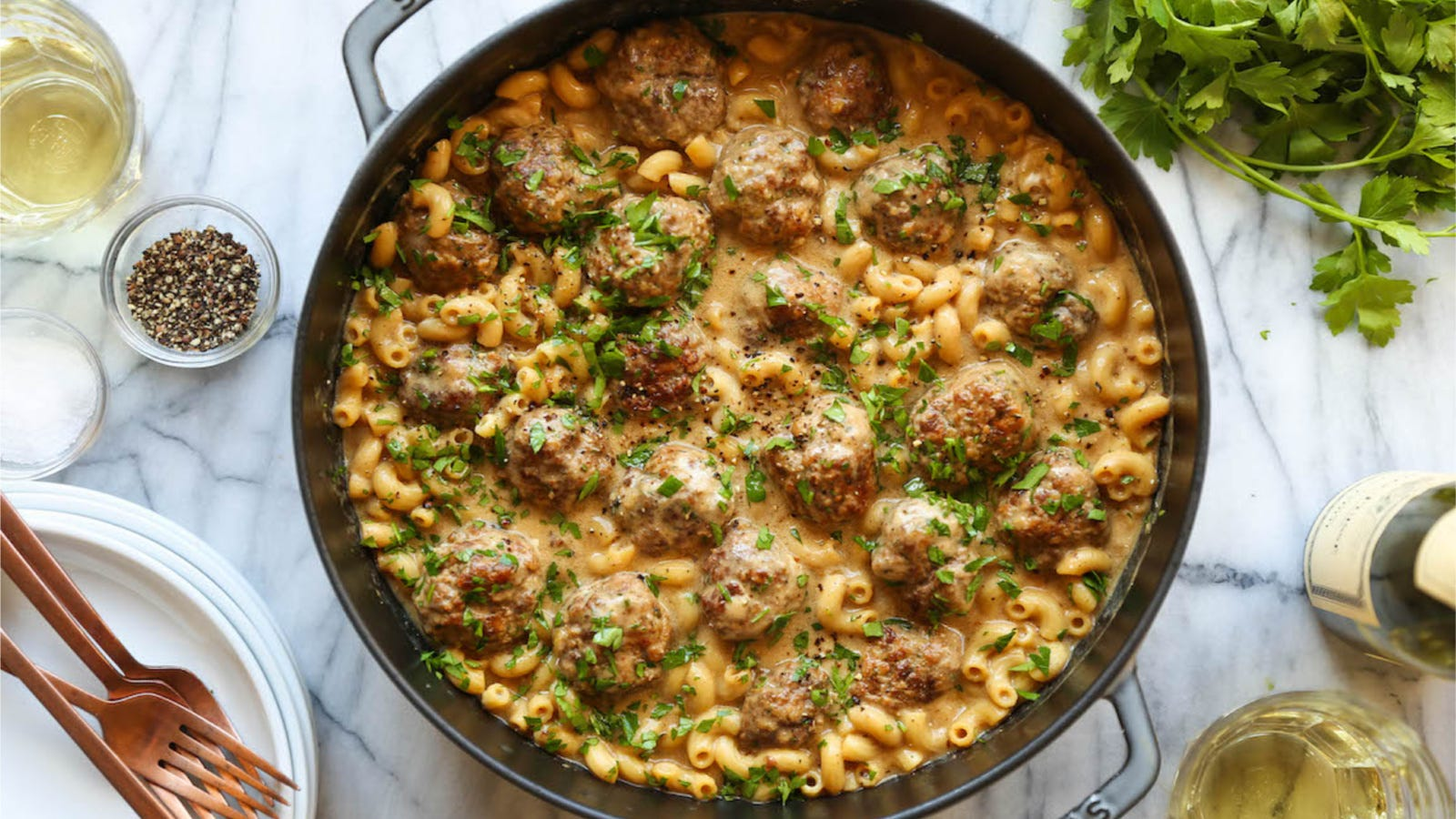 A large Staub Dutch oven filled with Swedish meatballs and macaroni elbows swimming in a beef gravy, topped with fresh parsley. Surrounding the Dutch oven are various ingredients and a few forks.