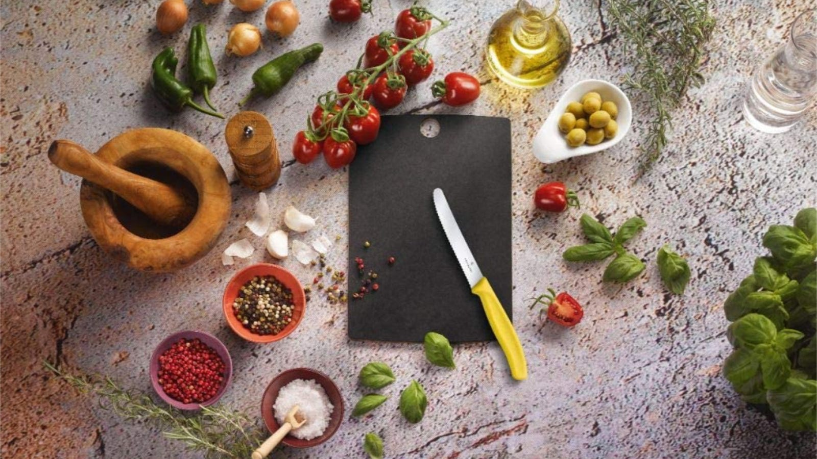 A small black cutting board with a serrated Victorinox knife with several aromatic ingredients surrounding the knife and board.