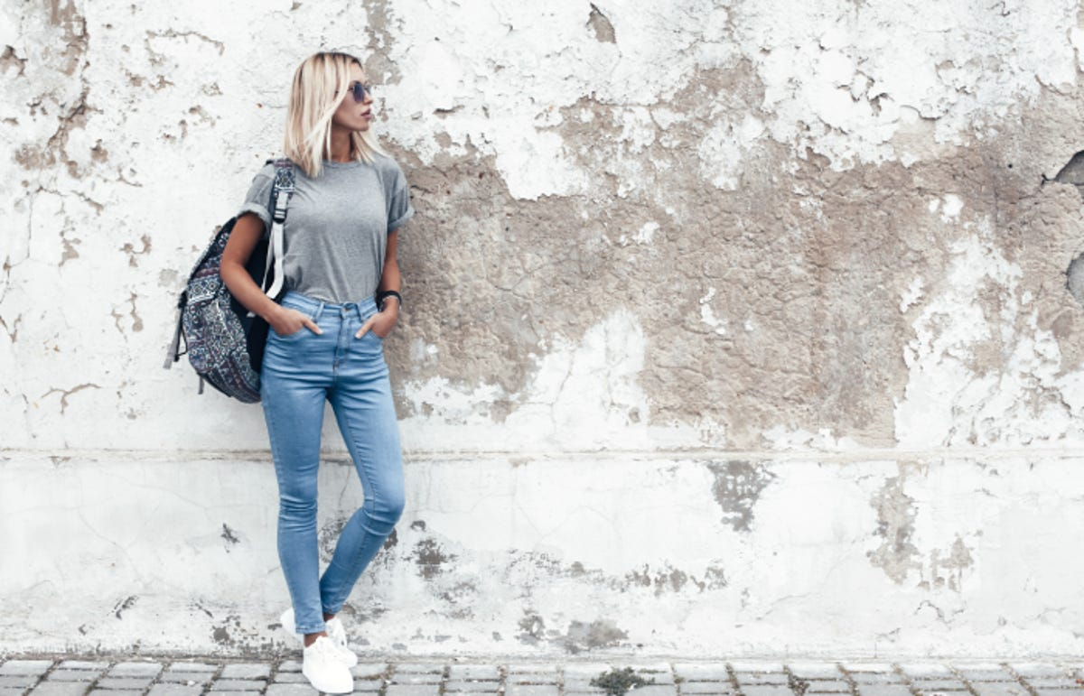 young blonde woman wearing high-waisted jeans and a backpack standing by old wall
