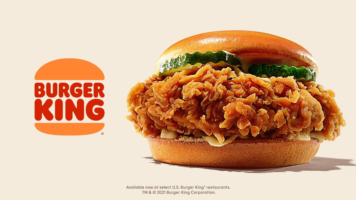 A fried chicken sandwich with pickles and sauce is placed next to the Burger King logo.