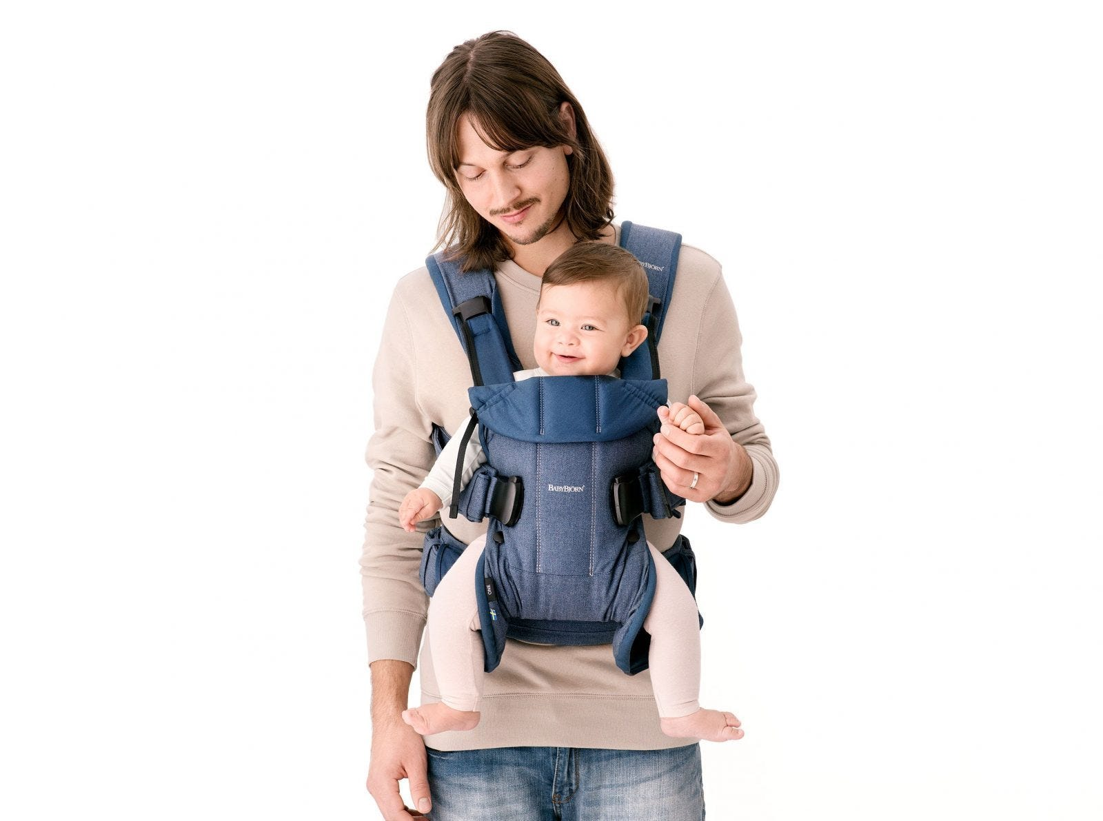 A man carrying a newborn in front in a BabyBjörn carrier.