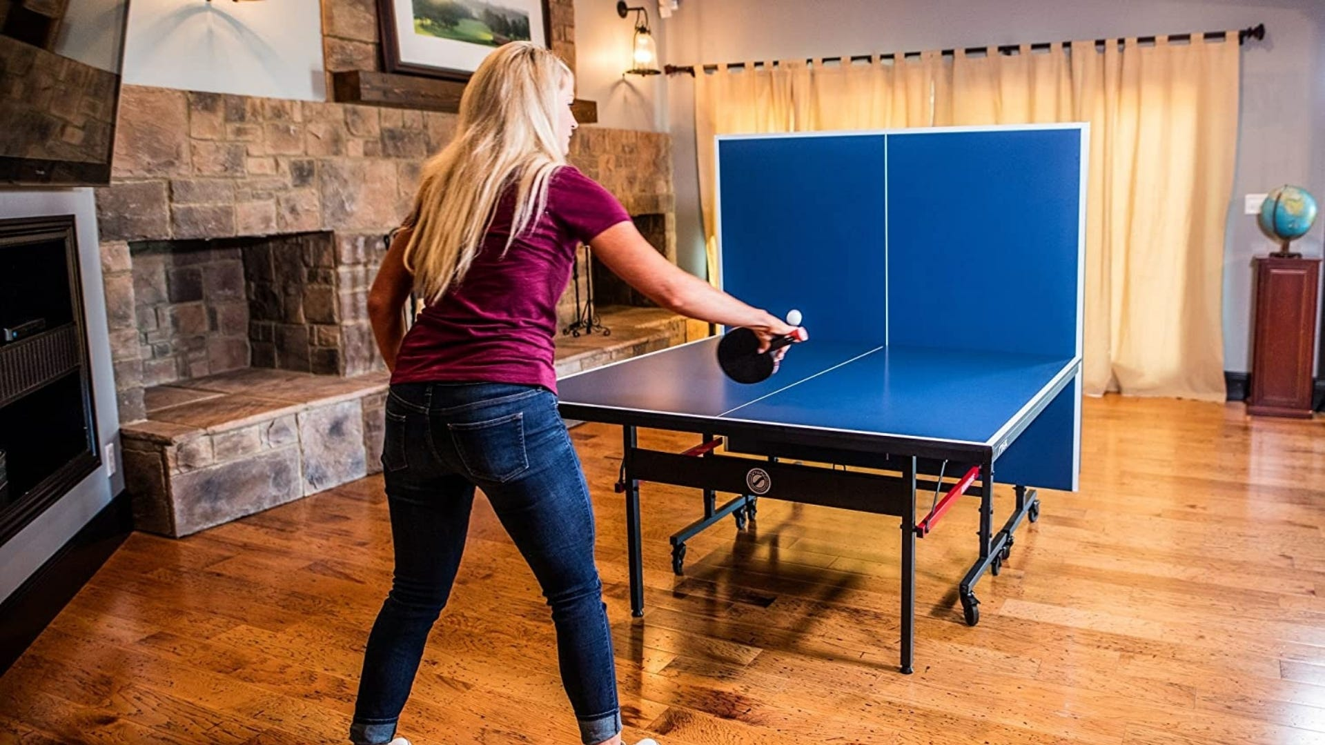 A girl playing ping-pong in a game room.