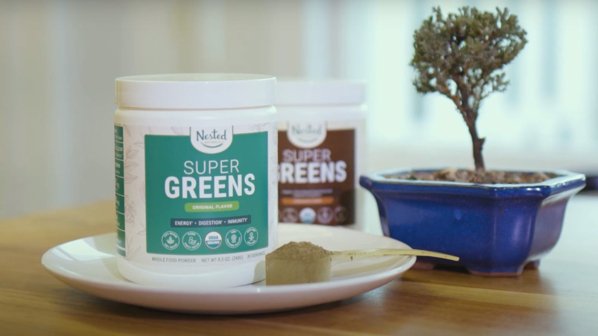 Two bottles of Nested Naturals Super Greens powder on a table.
