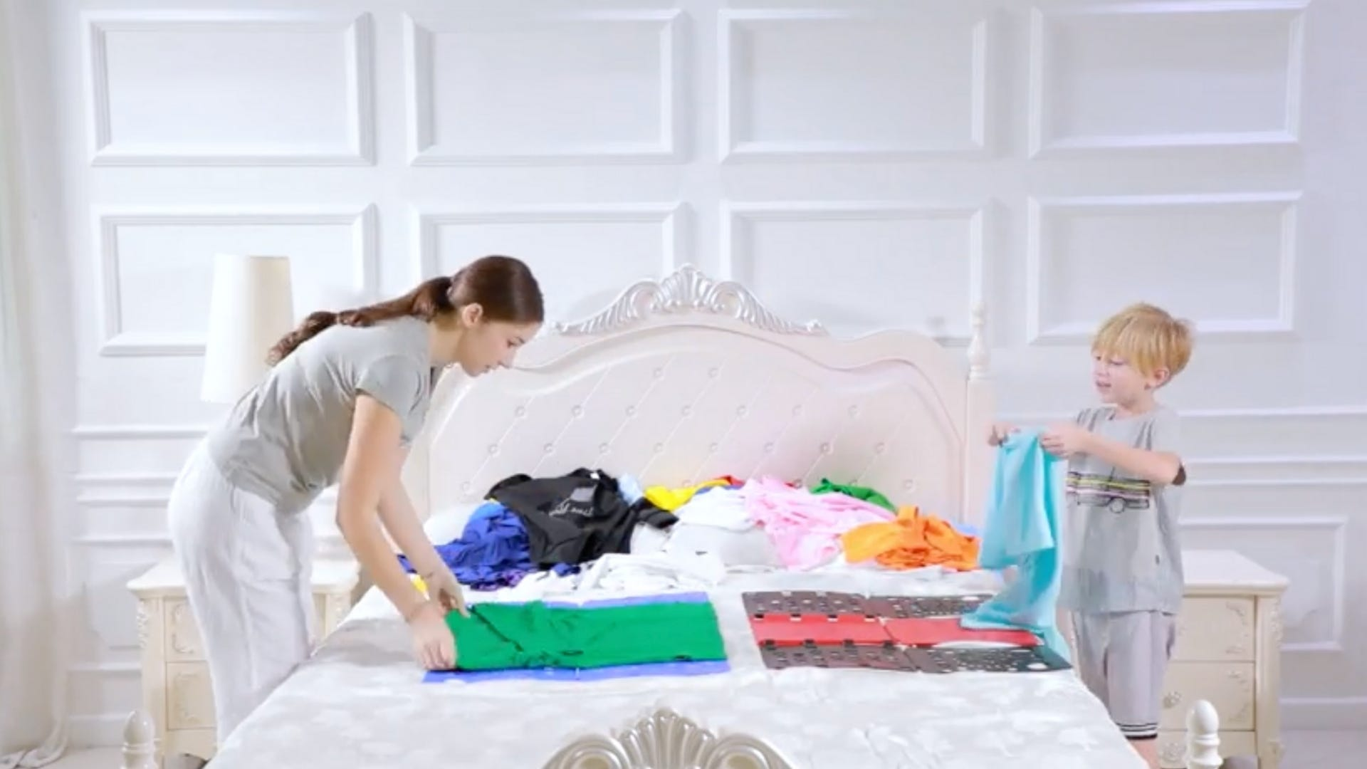 Mom and son folding clothes on a bed with the BoxLegend shirt folding board.