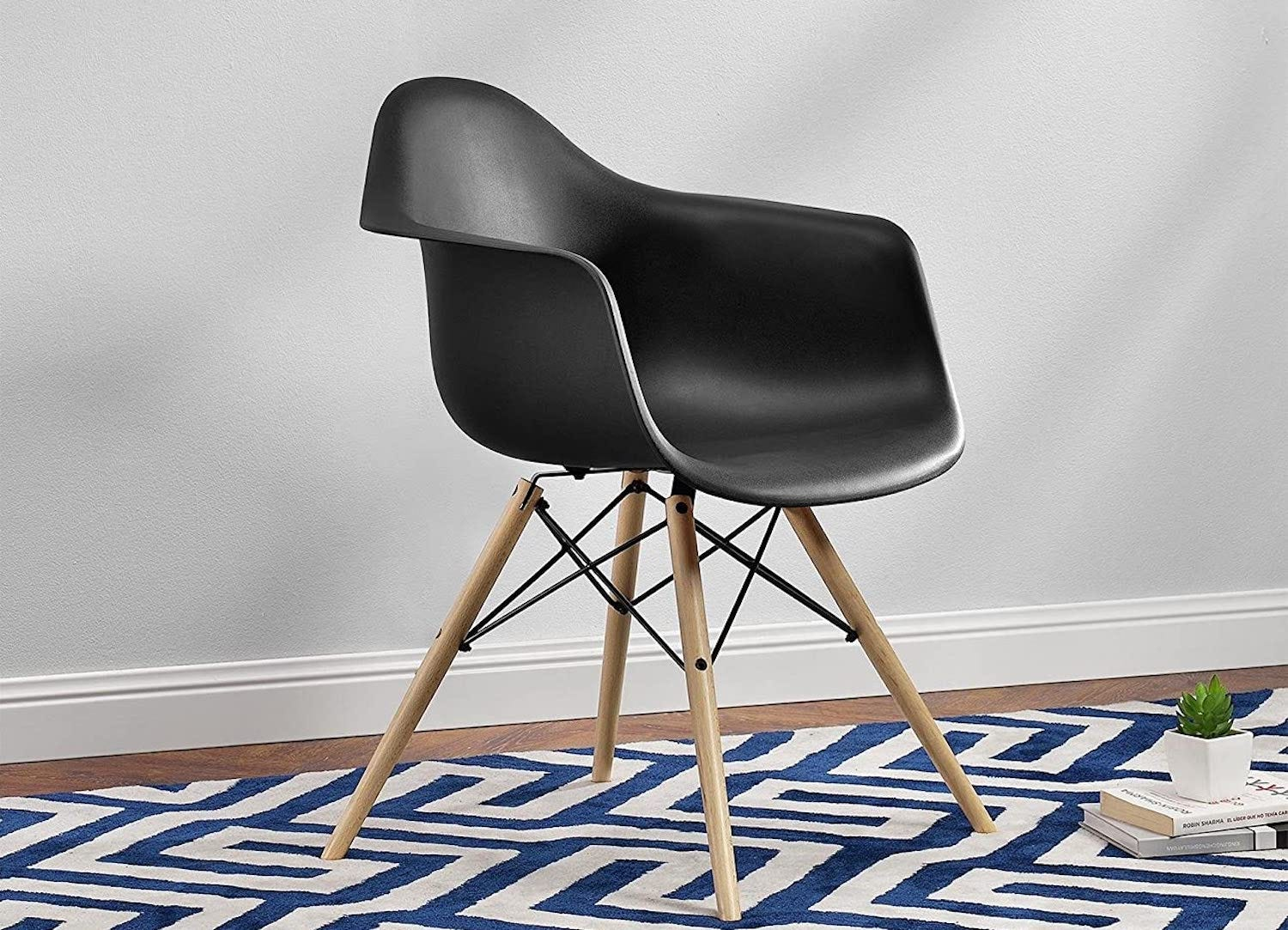 The DHP Mid-Century Modern Molded Chair in black sitting on a geometric-patterned rug.
