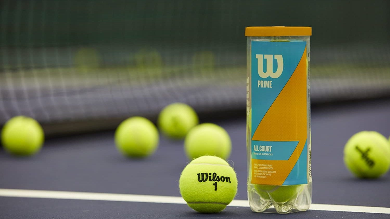 A Wilson tennis balls container surrounded by balls on a tennis court.