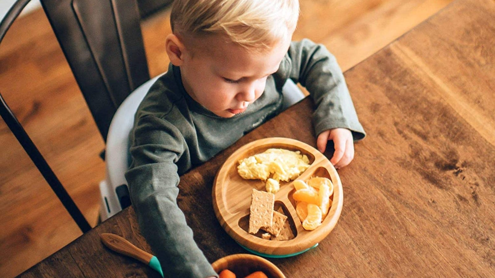 A toddler sitting at a table in front of the Avanchy wooden plate with eggs, orange slices, and graham crackers in each section.