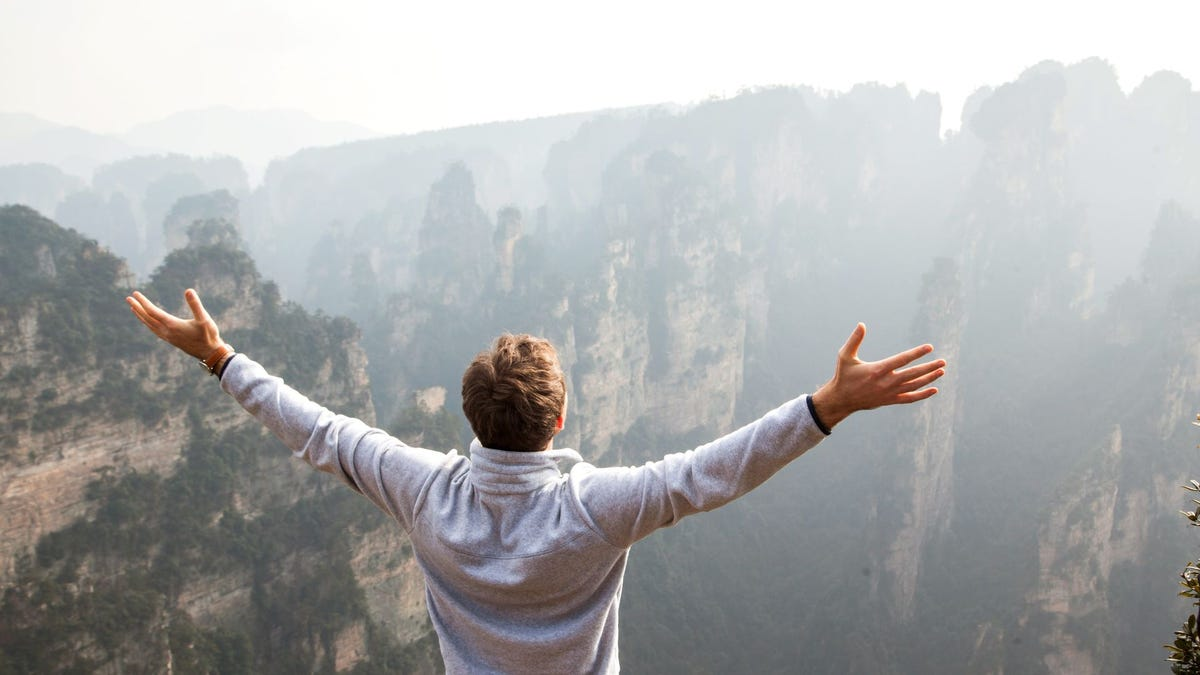 A man with arms outstretched overlooking a canyon.