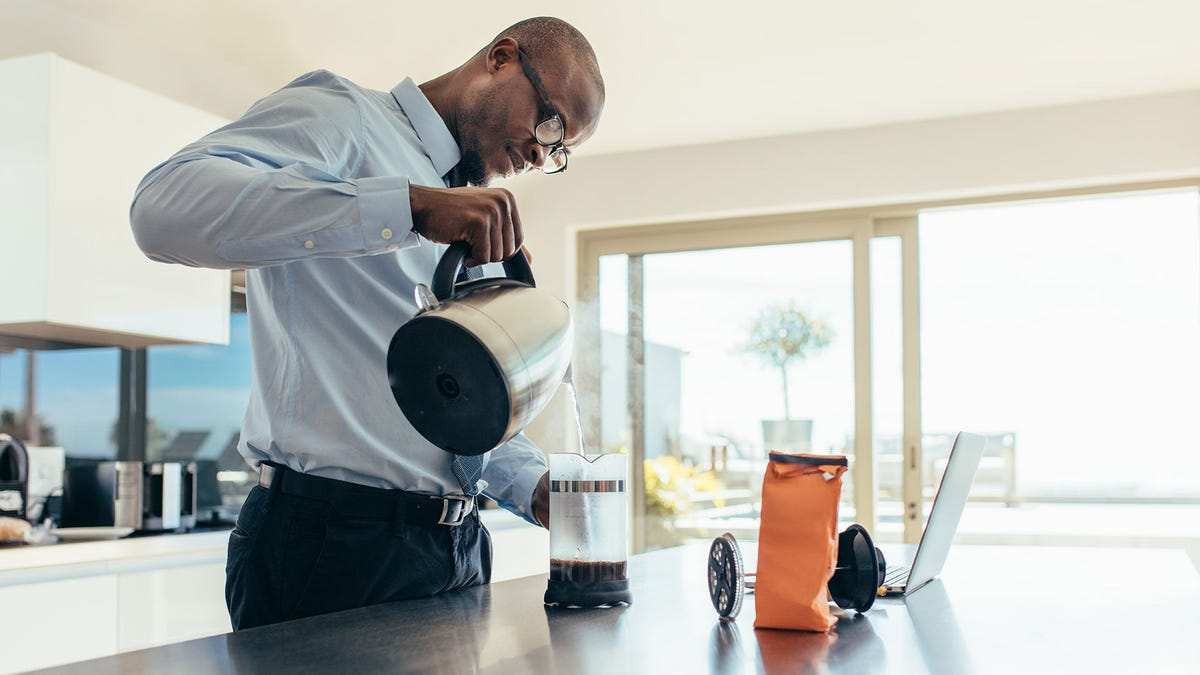 A man preparing coffee at home in a French press-style coffee maker.