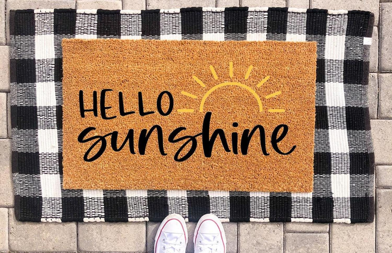 """A doormat with """"hello sunshine"""" and a sun design on it, sitting on a larger black and white check mat"""
