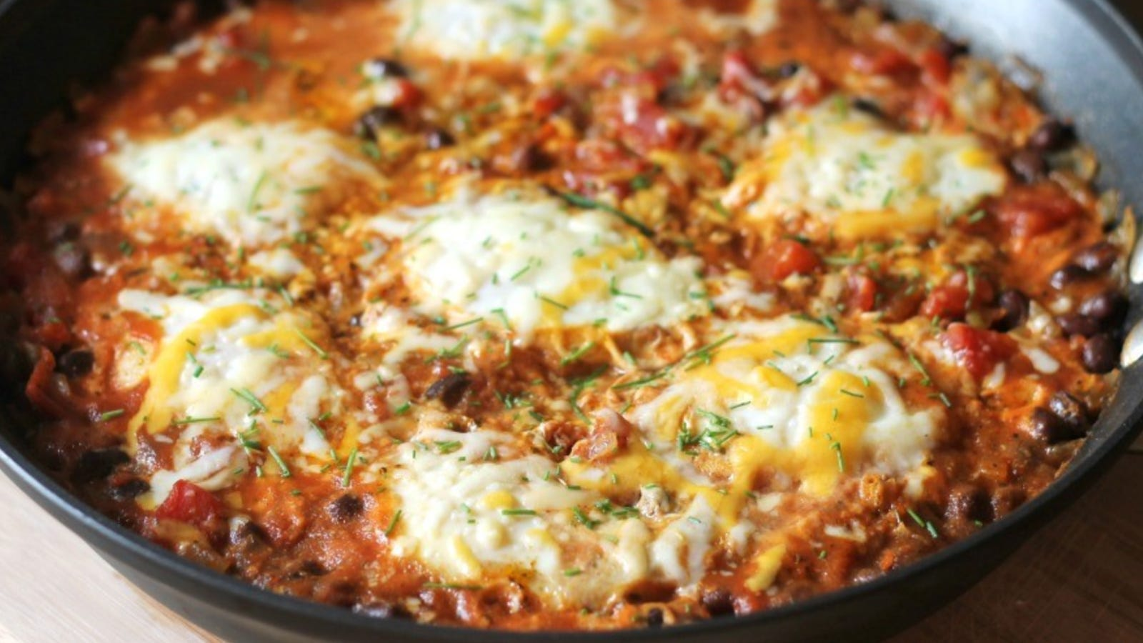 A large skillet filled with Mexican baked eggs topped with melted cheese.