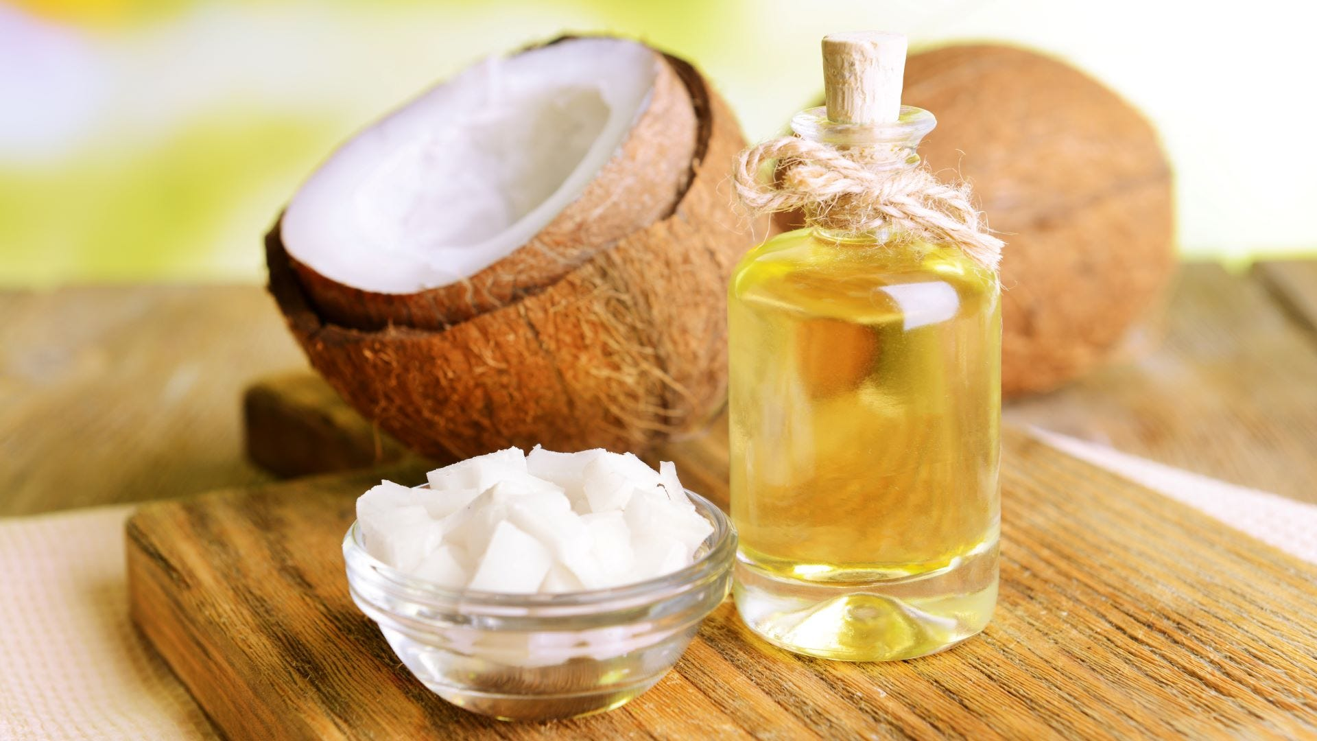 Coconut oil in a bottle next to coconuts.