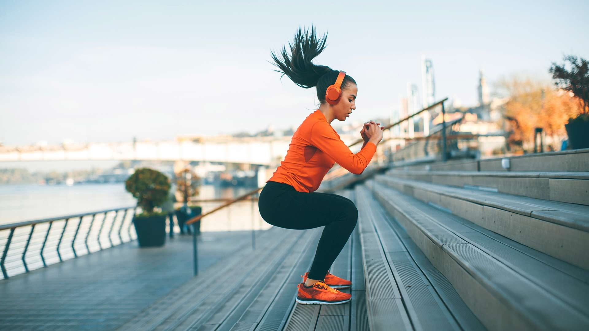 A woman doing jump-squat exercises on staircase in an urban park along a waterfront.