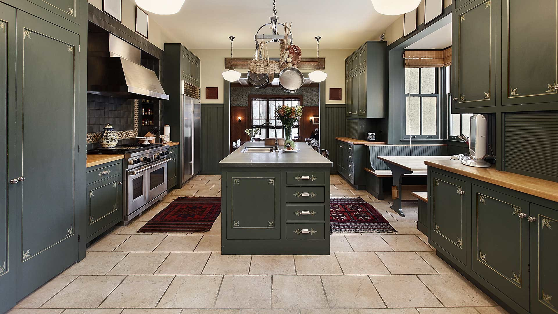 A beautiful kitchen with ceramic tiles and dark green cabinets.