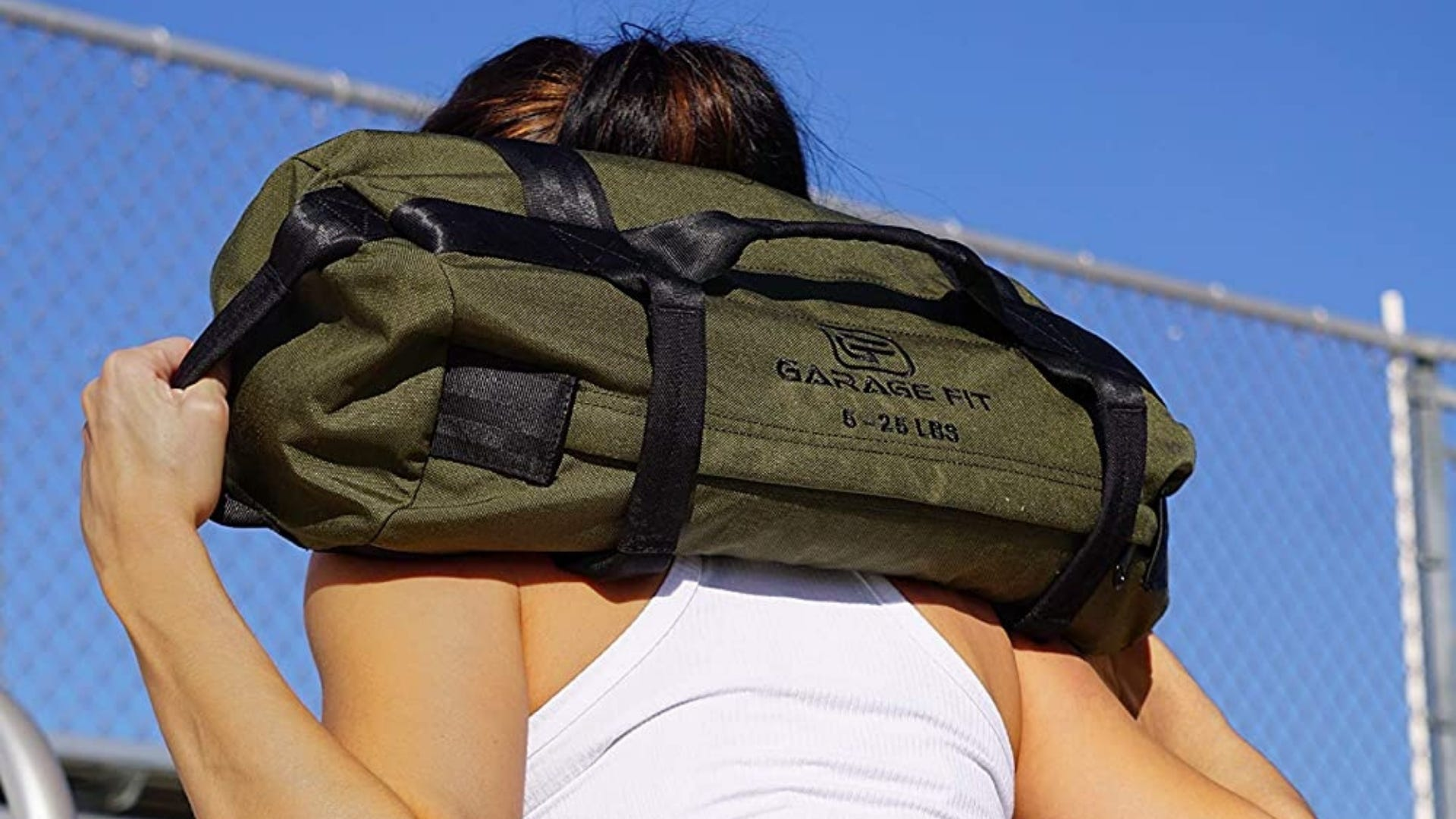 Woman is carrying green workout sandbag over her shoulders.