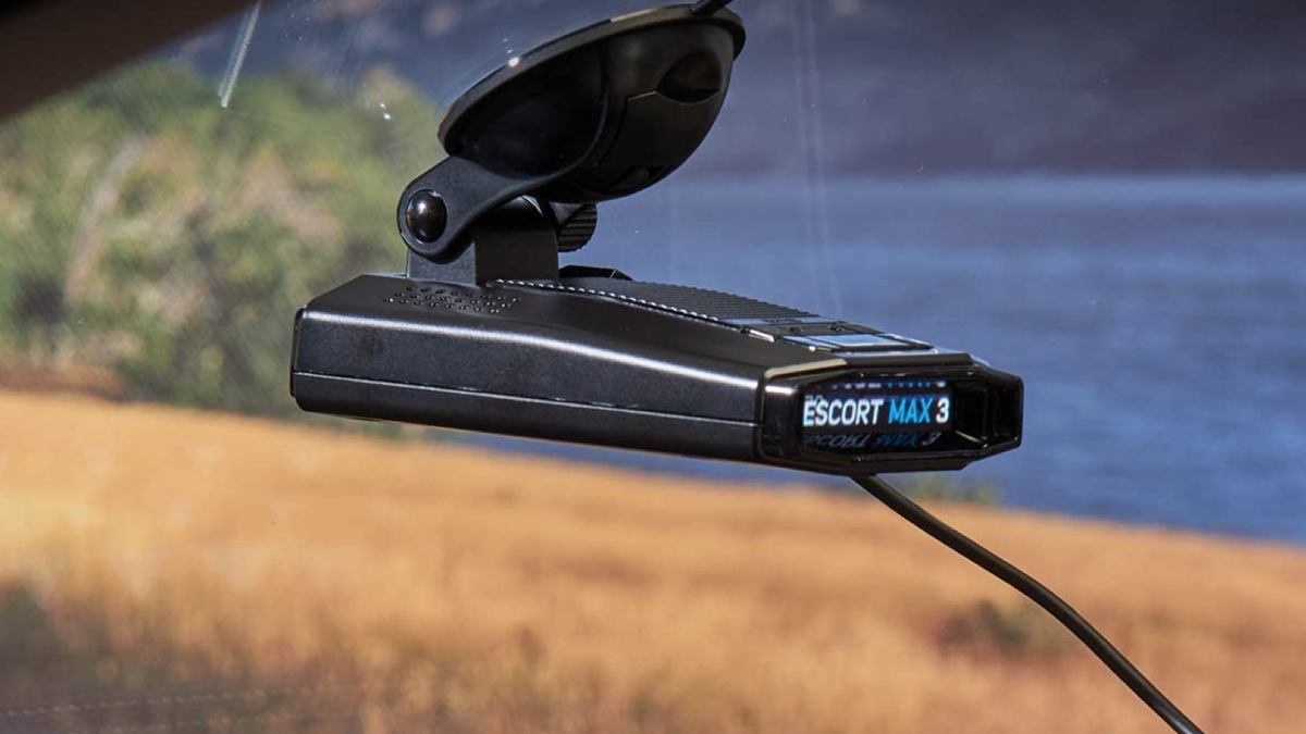 A side view of a black windshield-mounted radar detector mounted to a windshield with a lake in the background.